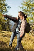 Young couple walking in meadow, man pointing
