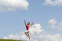 Young woman jumping in meadow, arms outstretched