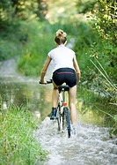 Girl riding through water on bike, rear view