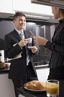 Executives in kitchen, man having coffee, woman holding mobile phone