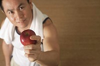 Man holding apple up to camera