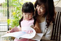 Grandmother and granddaughter looking at book