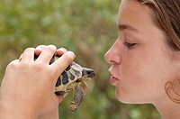 Girl holding turtle, profile