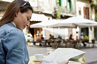 Woman Reading Map at Outdoor Cafe