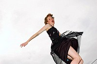 Girl in party dress jumping with excitement.