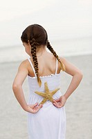 Rear view of a girl standing on the beach and holding a starfish behind her back