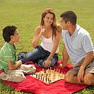 Side profile of a boy sitting with his parents and playing chess