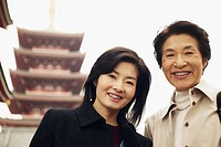 Low angle view of a mature woman and a mid adult woman in front of a pagoda