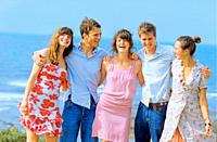 Teenagers standing with arms around each other on beach