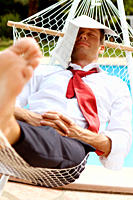 Businessman in hammock with newspaper on head