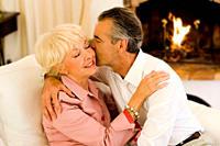 Senior couple hugging and kissing on sofa