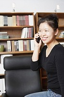 Close-up of a businesswoman using a mobile phone and smiling