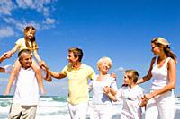 Multi-generational family walking on beach