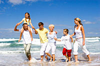 Multi-generational family walking in surf at beach