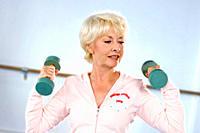 Senior woman using dumbbells indoors