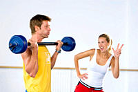Woman counting repetitions as man lifts barbell