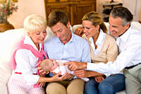 Multi-generational family smiling at baby