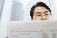 Close-up of a mature man reading a newspaper