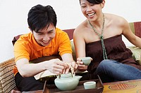 Close-up of a young couple with a kettle and coffee cups