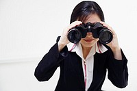 Close-up of a businesswoman looking through a pair of binoculars