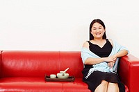 Portrait of a mid adult woman sitting on a couch and smiling