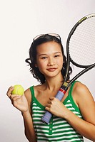 Portrait of a young woman holding a tennis racket and a tennis ball