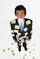 High angle view of a businessman standing with adhesive notes on his body
