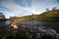 Man fishing in river at Lapland, Sweden