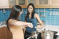 Two young women cooking in the kitchen