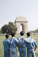 Rear view of four boys standing with their arms around each other in front of a monument, India Gate, New Delhi, India