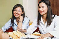 Close-up of two young women eating in a restaurant