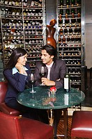 Businesswoman and a businessman sitting with glasses of wine in a wine cellar