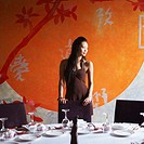 Young woman standing behind a table in a restaurant