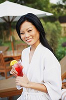 Portrait of a young woman smiling and holding a glass of juice