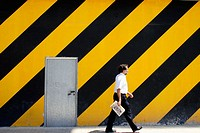 Man walking in front of striped wall
