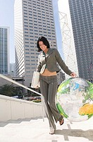 Businesswoman carrying a laptop and a transparent globe