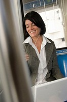 Businesswoman wearing headphones with a laptop on her lap