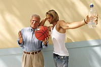 Portrait of a senior man holding a basketball and standing with his son