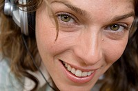 Portrait of a young woman wearing headphones and listening to music