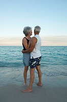 Side profile of a senior couple embracing each other on the beach