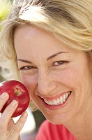 Close-up of a mid adult woman holding an apple and smiling