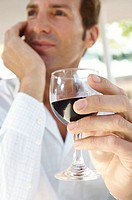 Low angle view of a mid adult man holding a glass of red wine