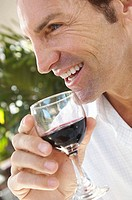 Close-up of a mid adult man holding a glass of red wine
