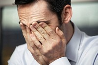 Businessman with hands on face