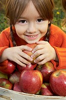 Girl with a pile of red apples