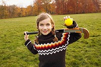 Girl holding field hockey equipment