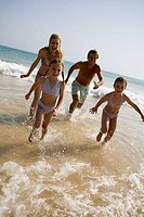 Family on beach running out of sea