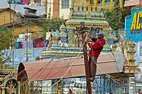 India. Tamil Nadu. Coonoor. Indian electrician working on wiring post in Coonoor.
