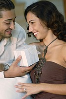 Close-up of a young man giving a gift to a young woman