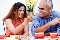 Mid adult woman feeding a spoonful of snacks to a mid adult man